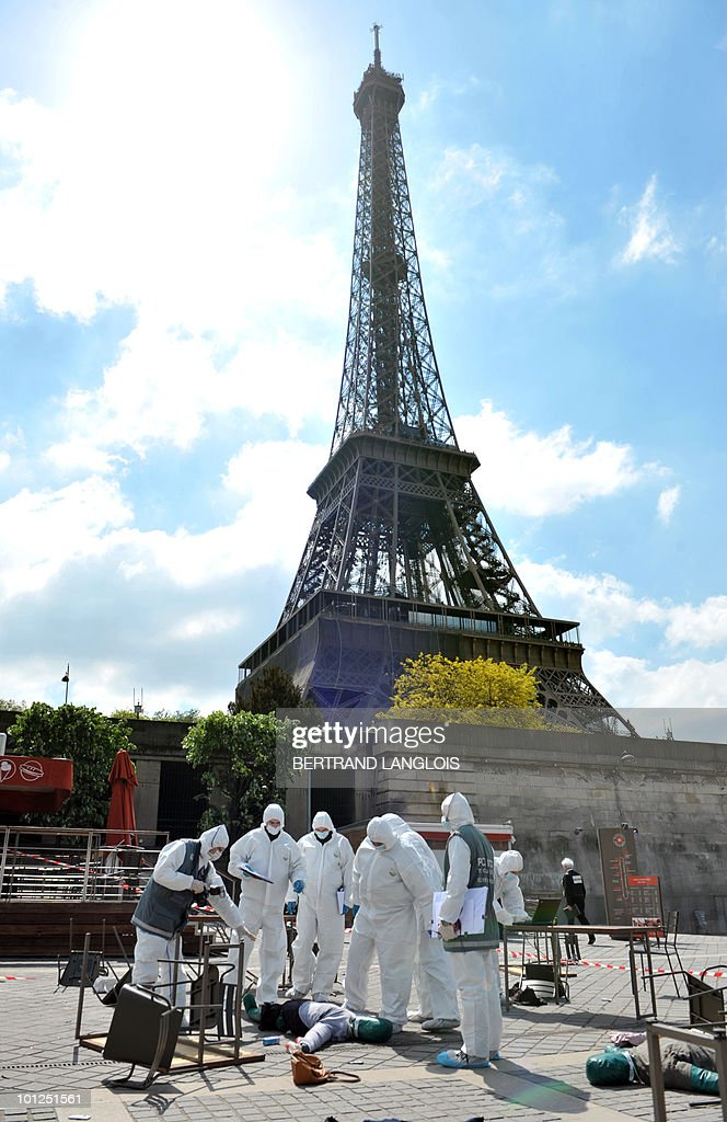 Rescuers wearing NBC suits prepare to evacuate a participant acting as an injured person during a multi attacks exercise on May 4, 2010 near the Eiffel Tower in Paris. Intitled 'Omega 2010', the exercise is organised by the Secretary General for the Zone of Defence and Security of the Prefecture of Police in several places in Paris and aims to train police forces to multi attacks.