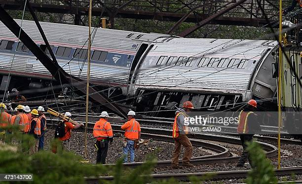 Rescuers work around derailed carriages of an Amtrak train in Philadelphia Pennsylvania on May 13 2015 Rescuers on May 13 combed through the mangled...