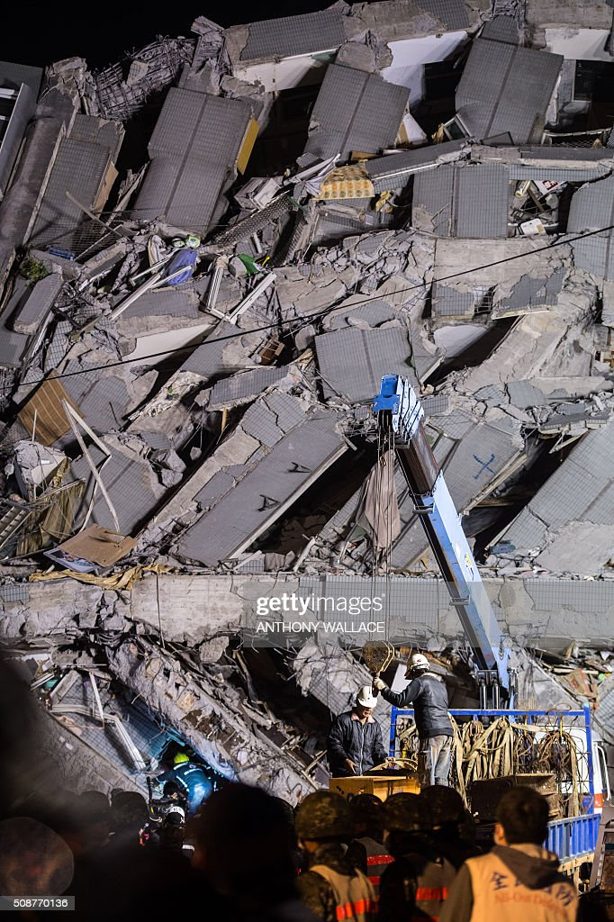 Rescuers work at a collapsed building in the southern Taiwanese city of Tainan following a strong 6.4-magnitude earthquake that struck early on February 6, 2016. Relatives of residents trapped in a 16-storey apartment complex felled by a powerful earthquake in Taiwan that killed 14 people were praying for miracles Saturday as rescuers sought survivors, with more than 150 missing in the quake zone. / AFP / ANTHONY WALLACE