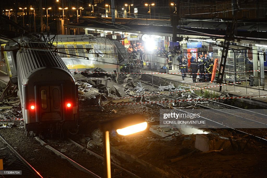 Rescuers work at night on the site of a train accident on July 12, 2013 at the railway station of Bretigny-sur-Orge, near Paris. At least six people were killed and dozens injured on Friday after a speeding train derailed at a station in the southern suburbs of Paris, officials said. AFP PHOTO / LIONEL BONAVENTURE