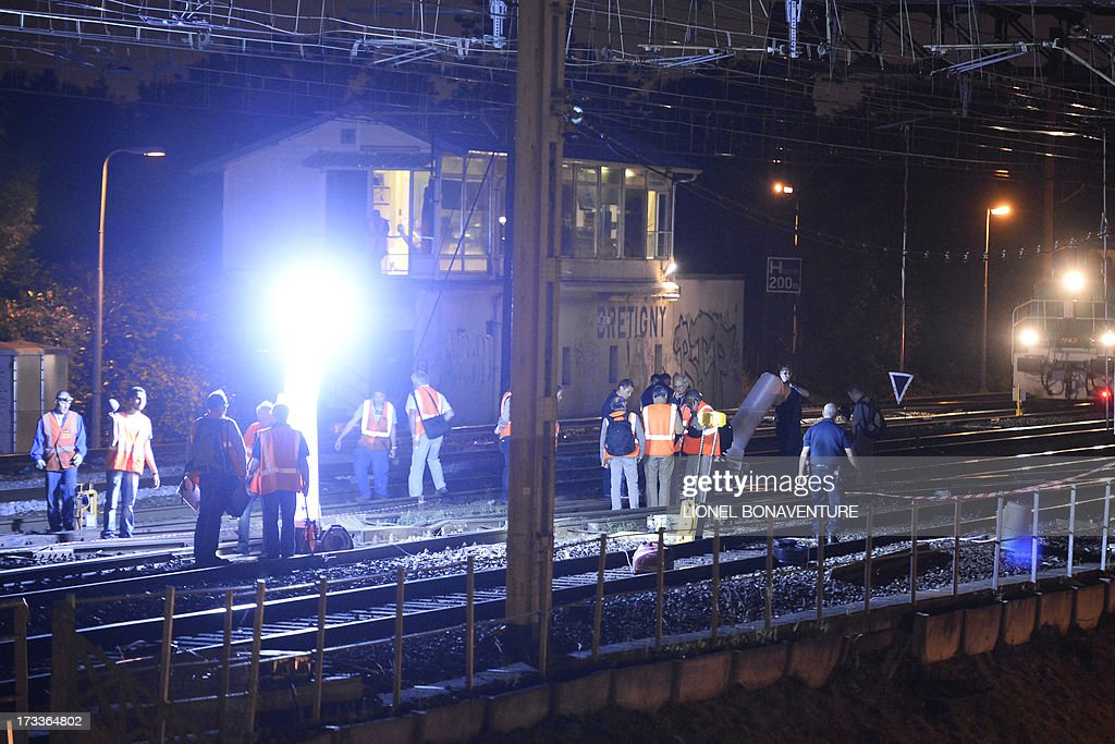 Rescuers work at night on the site of a train accident on July 12, 2013 at the railway station of Bretigny-sur-Orge, near Paris. At least six people were killed and dozens injured on Friday after a speeding train derailed at a station in the southern suburbs of Paris, officials said.