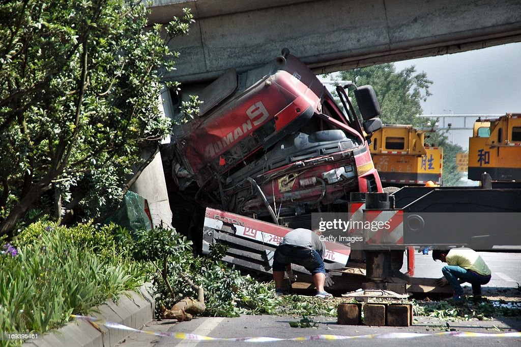 Rescuers work at the accident site on the west second ring road on May 23, 2013 in Guiyang, China. A bridge collapsed after a tanker crashed into one of its support. Another passing truck was struck, injuring two.