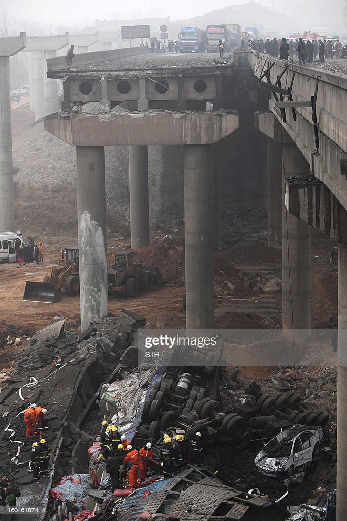 Rescuers (bottom) work at the scene of the collapsed Yichang bridge near the city of Sanmenxia, central China's Henan province, on February 1, 2013 after a fireworks-laden truck exploded as it crossed the bridge killing 26 people as the structure collapsed and vehicles plummeted to the ground, state-run media reported. An 80-metre long part of the bridge collapsed and six vehicles had been retrieved from the debris, China's official news agency Xinhua said. The bridge near the city of Sanmenxia is on the G30 expressway, the longest road in China, which stretches for nearly 4,400 kilometres (2,700 miles) from China's western border with Kazakhstan to the eastern Yellow Sea.