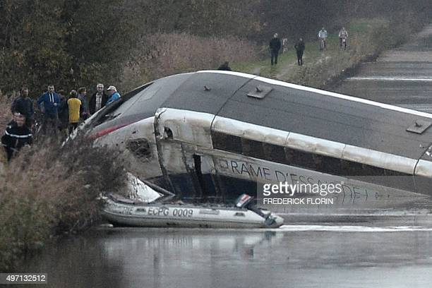 Rescuers work at the scene where a highspeed TGV train coach and engine carriage lie in a canal in Eckwersheim near Strasbourg northeastern France...