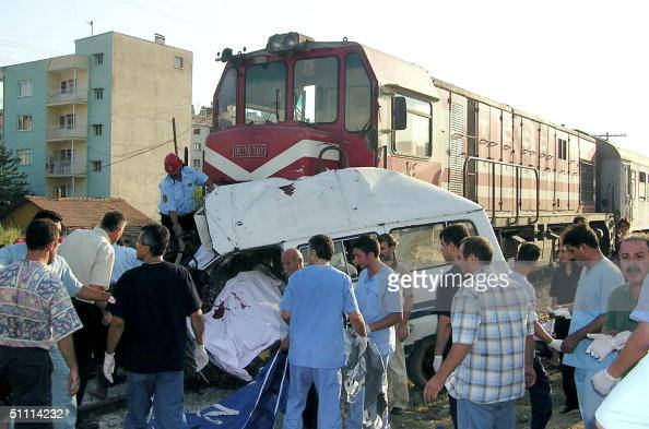Rescuers work at the site where a train crashed into a minibus killing 10 people and injuring six more in Adiyaman western Turkey 25 July 2004