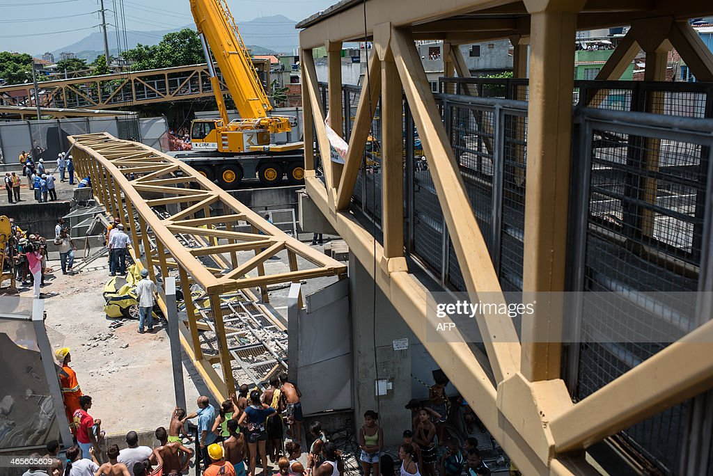 Rescuers work by a taxi crushed by a pedestrian bridge over the Linha Amarela (the yellow line) road in Rio de Janeiro, Brazil, on January 28, 2014. A pedestrian overpass spanning a busy road in Rio de Janeiro collapsed after being struck by a truck on Tuesday, killing four people below, officials said. At least four people were also injured in the accident. A pedestlian bridge falls on a taxi after a truck hit the bridge on the yellow line expressway in Rio de Janeiro, Brazil on January 28, 2014. 2014.