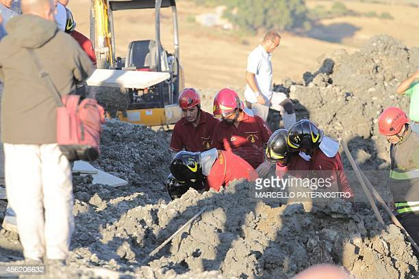 Rescuers work on the site of a sudden eruption of a mud geyser at the Natural reserve of Maccalube in Aragona Sicily that killed a sevenyearold girl...
