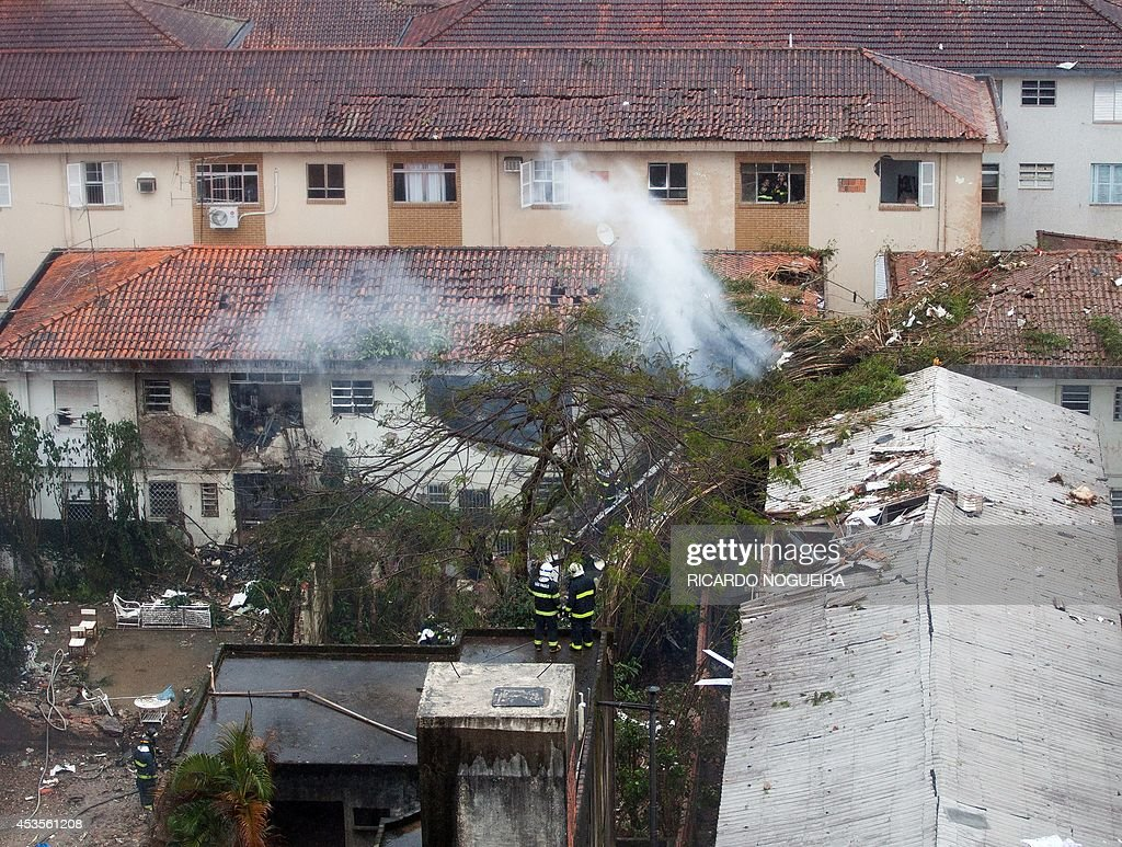 Rescuers work on the site of the crash of the Cessna 560XL aircraft carrying the presidential candidate of the Brazilian Socialist Party (PSB) party Eduardo Campos in Santos, Sao Paulo state, Brazil, on August 13, 2014. The plane failed to land and crashed into a gymnasium and two homes and several people died in the accident, including all its passengers. AFP PHOTO/Ricardo Nogueira