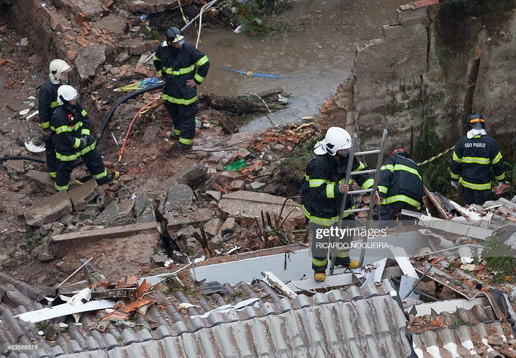 Rescuers work on the site of the crash of the Cessna 560XL aircraft carrying the presidential candidate of the Brazilian Socialist Party (PSB) Eduardo Campos in Santos, Sao Paulo state, Brazil, on August 13, 2014. The plane failed to land and crashed into a gymnasium and two homes and several people died in the accident, including all its passengers.