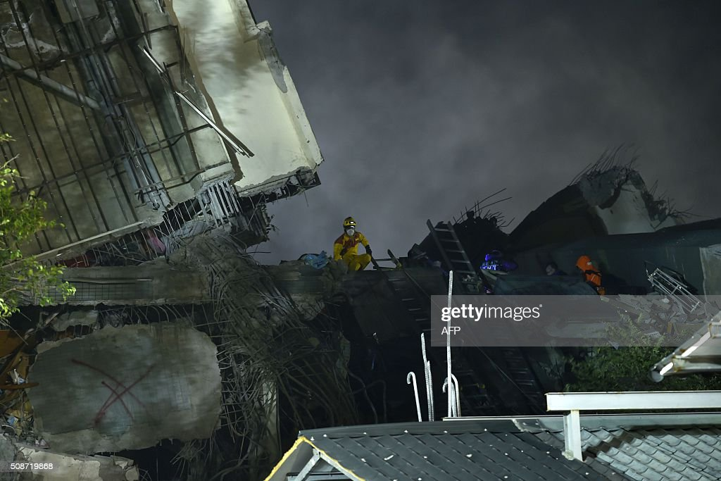 Rescuers work over rubble at the site of a collapsed building in the southern Taiwanese city of Tainan on February 6, 2016 following a strong 6.4-magnitude earthquake. A powerful earthquake in Taiwan felled a 16-storey apartment complex full of families who had gathered for Lunar New Year celebrations in the early hours of February 6, with at least seven dead and more than 30 feared trapped. AFP PHOTO / Sam Yeh / AFP / SAM YEH