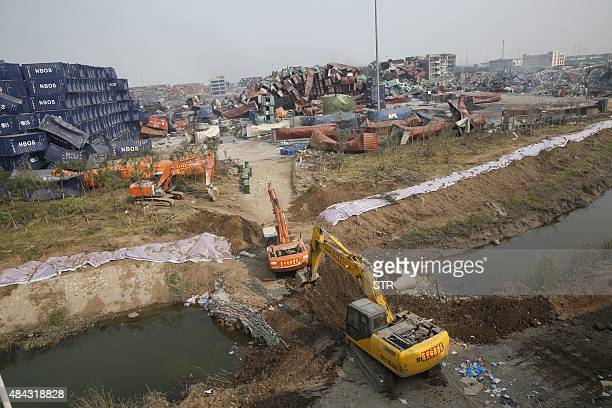 Rescuers work to build up a temporary barrier in Tianjin on August 17 2015 at the site of the explosions last week that hit a chemical warehouse...
