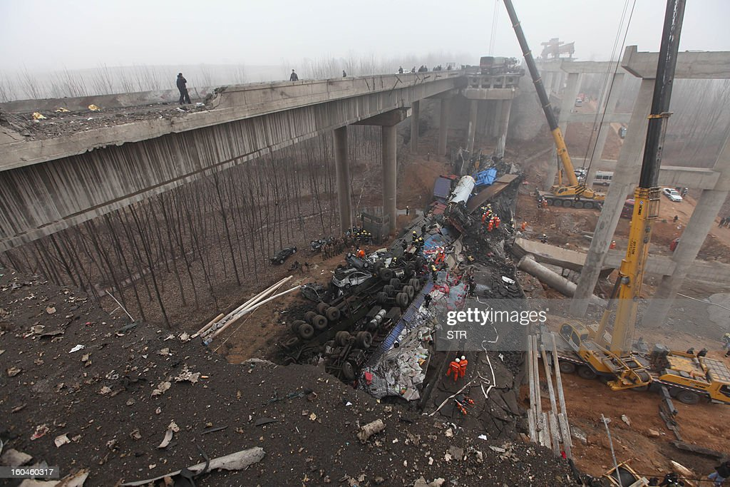 Rescuers work under the collapsed Yichang bridge near the city of Sanmenxia, central China's Henan province, on February 1, 2013. A fireworks-laden truck exploded as it crossed a bridge in central China on February 1, killing 26 people as the structure collapsed and vehicles plummeted to the ground, state-run media reported. An 80-metre long part of the bridge collapsed and six vehicles had been retrieved from the debris, China's official news agency Xinhua said. The bridge near the city of Sanmenxia is on the G30 expressway, the longest road in China, which stretches for nearly 4,400 kilometres (2,700 miles) from China's western border with Kazakhstan to the eastern Yellow Sea. AFP PHOTO CHINA OUT