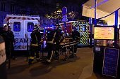 Rescuers workers evacuate a man on a stretcher near the Bataclan concert hall in central Paris on November 13 2015 A number of people were killed and...