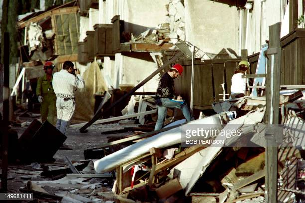 Rescues workers view the destruction of the Northridge Meadows Apartments early on january 18 1994 after an earthquake collapsed the structure...