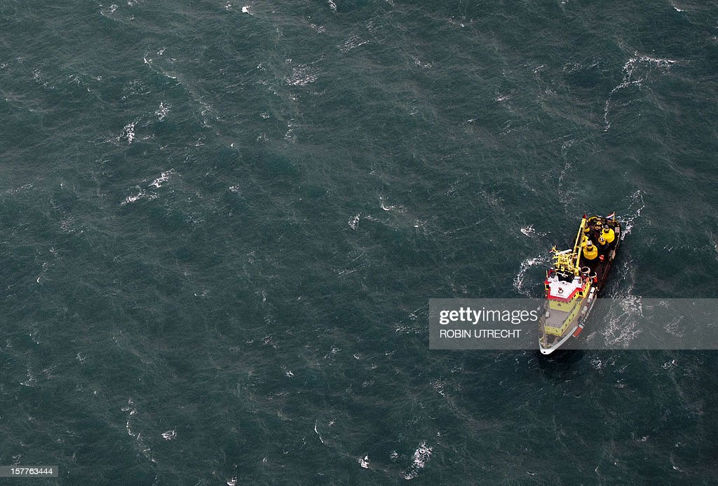 A rescue-vessel takes part in a search and rescue operation for crewmembers of the sunken cargo-vessel the Baltic Ace out from the sea during a rescue operation on December 6 in the North Sea. Dutch sea rescue services launched a major rescue operation for 11 missing sailors after two ships collided in a busy North Sea shipping lane off the coast of Rotterdam with one ship sinking. Rescuers, including the Dutch navy, on December 5, plucked 13 survivors from the water after the Baltic Ace car carrier collided with the Corvus J container ship about 100 kilometres (60 miles) southwest of Rotterdam. A Belgian sea rescue helicopter found another body this morning, the coastguard said, bringing the confirmed death toll to five. Late on December 6 Dutch coastguards called off a search for six crew still missing after their cargo ship sank in the North Sea, saying there was 'zero' chance of finding survivors in the icy waters.AFP PHOTO / ANP / ROBIN UTRECHT