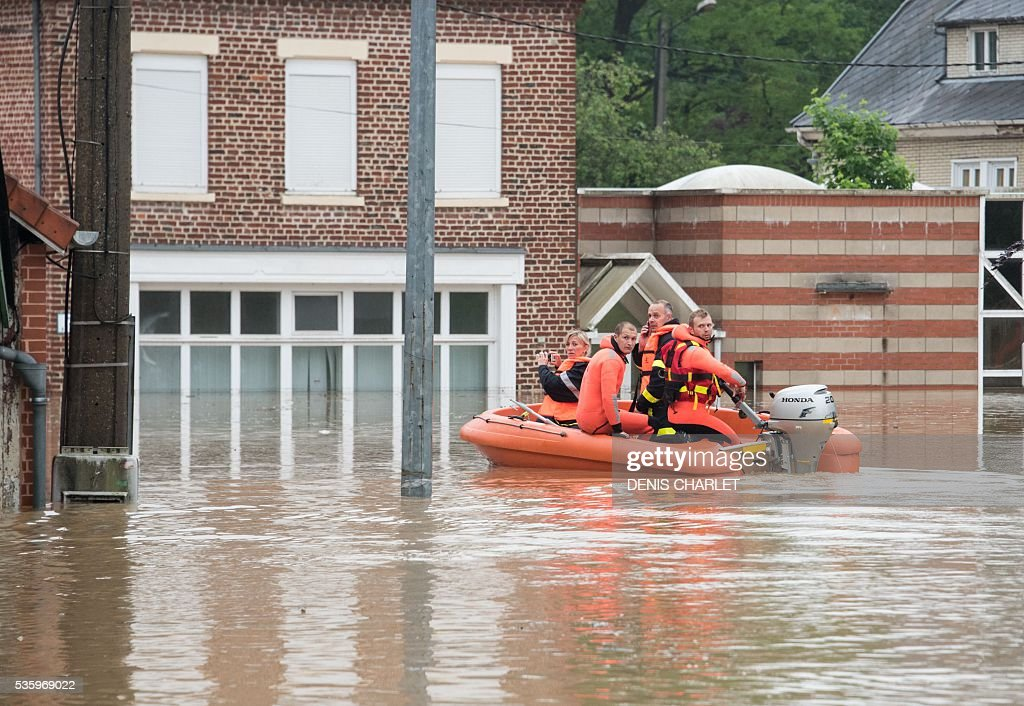 Rescuing firefighters patrol aboard a dinghy through the flooded town of Bruay-la-Buissiere, near Lens, northern France, on May 31, 2016, following heavy rainfalls. France's weather agency Meteo France maintained today 18 departments under orange alert for heavy rainfalls, which have already disrupted transports in the northeastern part of the country. / AFP / DENIS