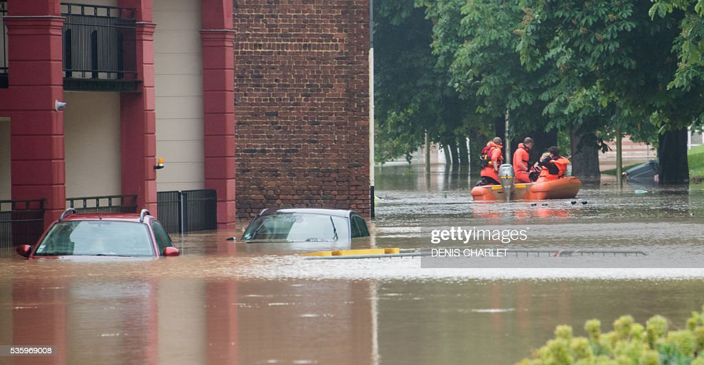 Rescuing firefighters patrol near submerged cars aboard a dinghy through the flooded town of Bruay-la-Buissiere, near Lens, northern France, on May 31, 2016, following heavy rainfalls. France's weather agency Meteo France maintained today 18 departments under orange alert for heavy rainfalls, which have already disrupted transports in the northeastern part of the country. / AFP / DENIS