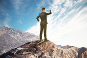 Research concept with businessman standing on mountain top, looking into the distance on clear sky background