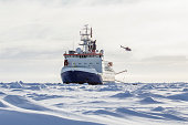 Research icebreaker docked to an ice floe and and a helicopter recently took off from the helideck while setting up an ice camp