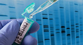 Hand holding vial doing CRISPR genomic research ++ DNA created in graphics program++