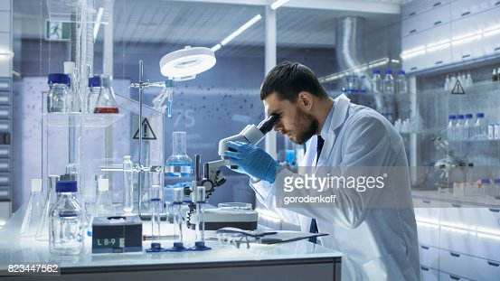 Research Scientist Looks into Microscope. He's Conducts Experiments in Modern Laboratory. : Foto de stock