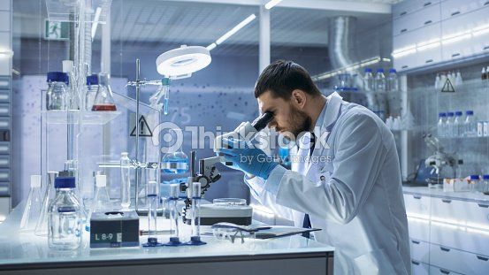 research scientist looks into microscope hes conducts experiments in