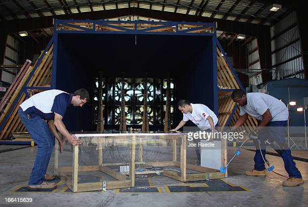 Research scientists James Erwin Jimmy Fu and Curtis Francisque adjust a box filled with sensors to be used to test wind pressure in front of twelve...