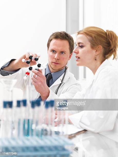 Researcher and doctor looking at a molecular structure