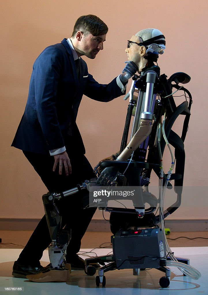 Researcher Bertolt Meyer, a lifelong user of prosthetic technology and the model for 'Rex', the world's first 'bionic man', poses with the humanoid during a photo call at the Science Museum in London on February 5, 2013. The 640,000 GBP (1 million US dollars) bionic has a distinctly human shape and boasts prosthetic limbs, a functional artificial blood circulatory system complete with artificial blood, as well as an artificial pancreas, kidney, spleen and trachea. Rex will be displayed at the Science Museum from February 7. AFP PHOTO/ANDREW COWIE