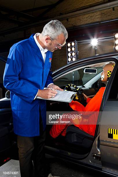 A researcher checking a crash test dummy