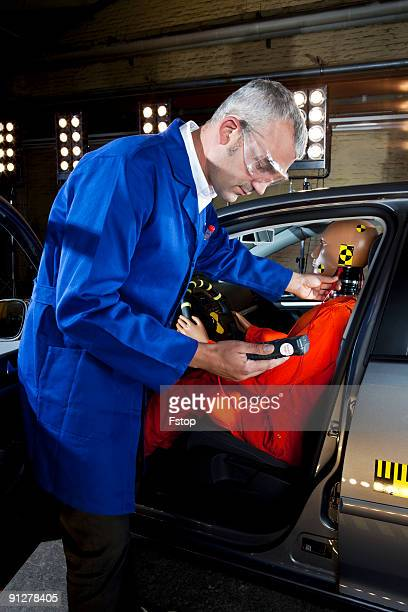 A researcher checking a crash test dummy with a me
