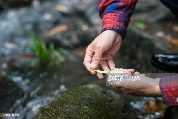 Een onderzoeker lakmoespapier monsters in het veld te controleren om te bepalen kwaliteit van het water