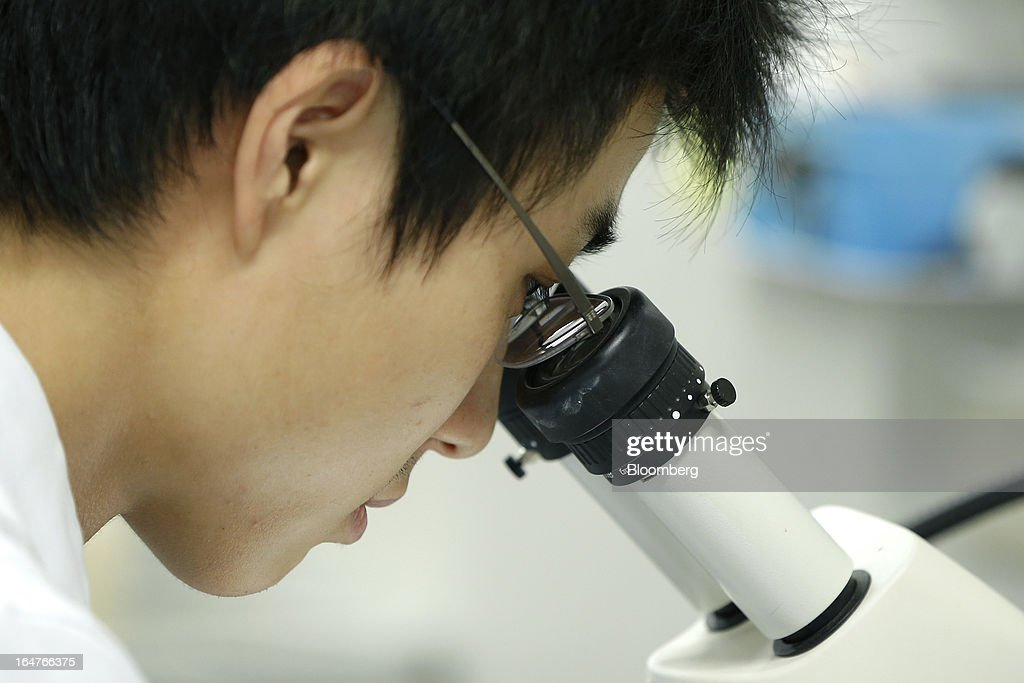 A researcher conducts cellular analyses as he looks through a microscope in a laboratory at Yokohama City University's (YCU) Advanced Medical Research Center (AMRC) in Yokohama City, Kanagawa Prefecture, Japan, on Monday, March 18, 2013. Japan aims to be a nation with the most advanced medical technologies and healthcare services in the world and to develop the medical industries for the revitalization of the country's economy. Photographer: Kiyoshi Ota/Bloomberg via Getty Images