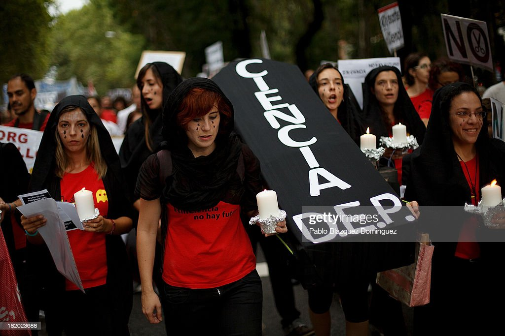 Researcher Elvira Bailon (C) 32, carries a cardboard cut out of a coffin with other scientists reading 'R.I.P. Science' during a demonstration against R&D cuts for sciences on September 27, 2013 in Madrid, Spain. Young Spanish scientists have called for a demonstration during the European Researchers' Night under the header, 'No Sciences, No Future', in response to cutbacks in research and development for Sciences. They claim that many Spanish researchers are leaving the country to find a jobs.