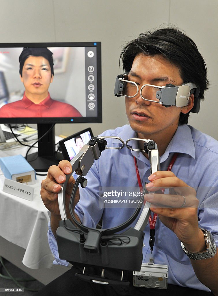 A researcher from NTT DoCoMo demonstrates a prototype model of a hands-free videophone at a press preview in Tokyo on September 19, 2012. The images taken by multiple, wide-angle cameras in the frames make the other person feel as if they are right in front of the user. AFP PHOTO / Yoshikazu TSUNO