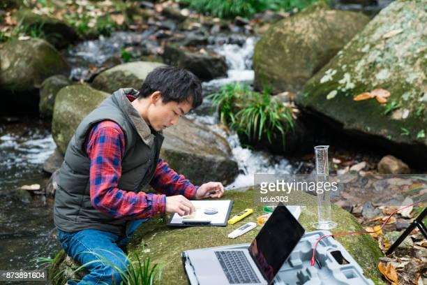 Een onderzoeker die het verzamelen van gegevens uit een zoet water stroom