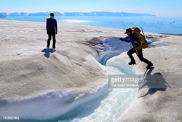 A researcher jumps a stream made by the melting glacier while the surface of the glacier is covered by cryoconite on July 18 2012 near Qaanaaq...