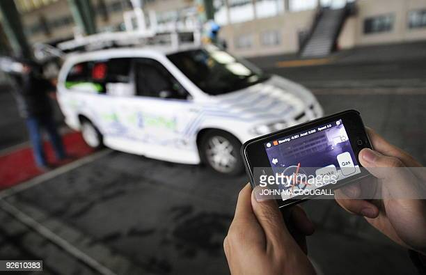 Researcher Miao Wang poses with an iPhone equipped with a remote interface to drive the 'Spirit of Berlin' an autonomous car which can be remotely...
