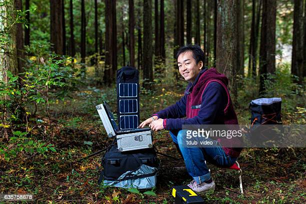 Researcher monitors the forest with a solar powered field laboratory