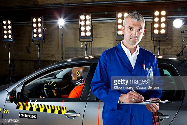 A researcher next to a car with a crash test dummy in a crash test laboratory