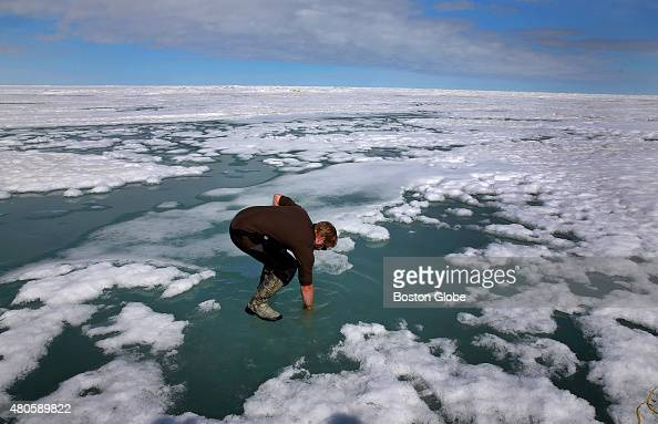 Researcher technician Josh Jones reaches his arm into melted Arctic ice to see how salty the water may be at Barrow Alaska