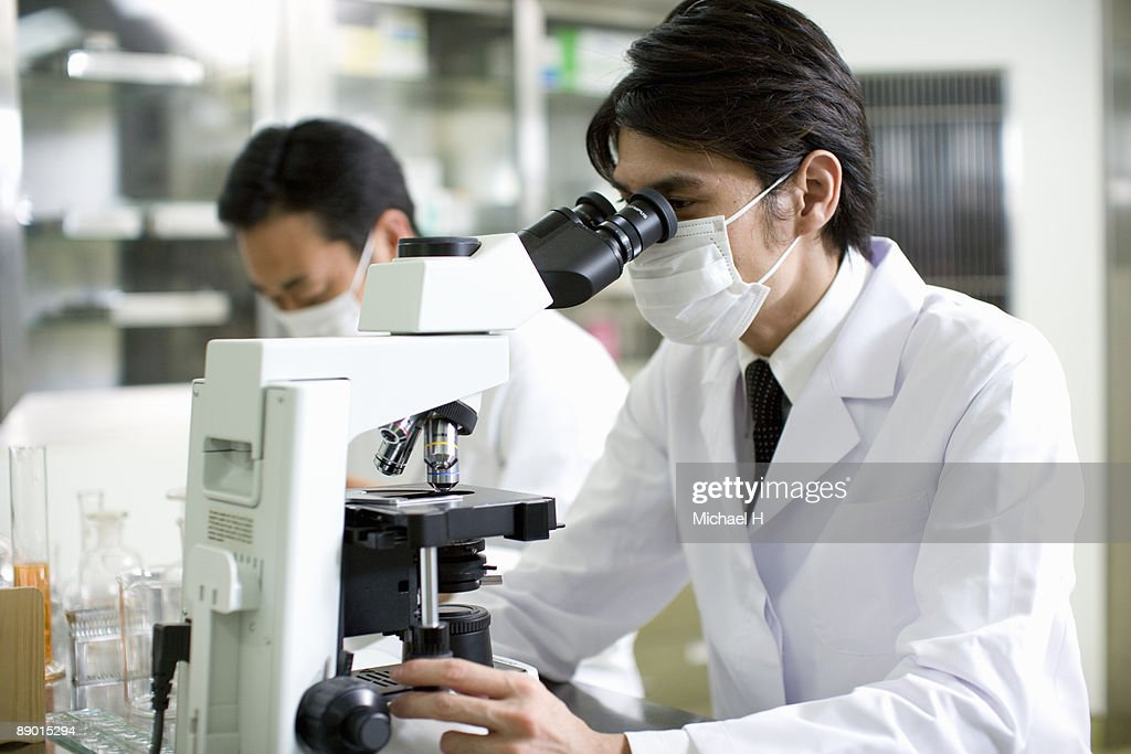 Researcher who looks through microscope : Stock Photo