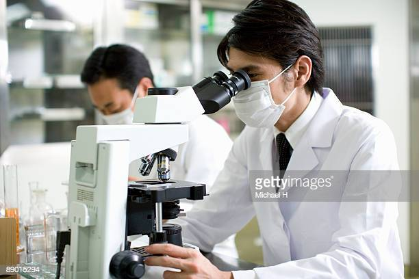 Researcher who looks through microscope