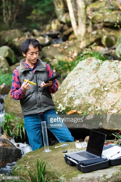 Onderzoeker met digitale tablet controleren de kwaliteit van het water van een rivier