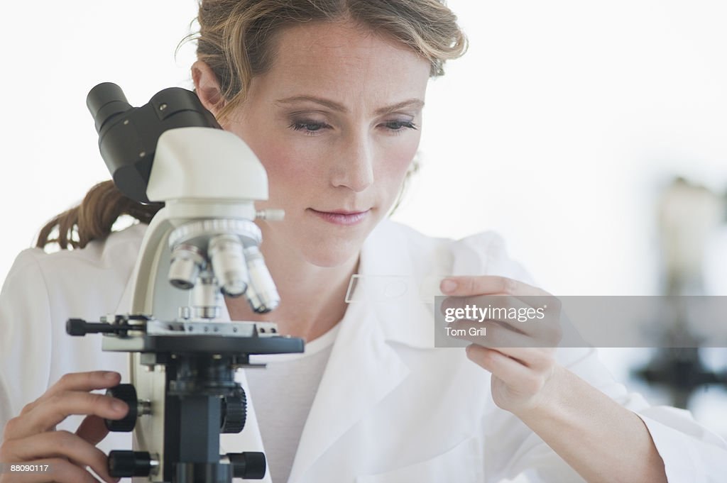 Researcher with microscope : Stock Photo
