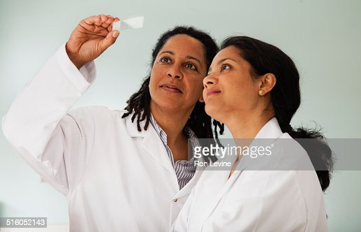 Researchers comparing slides in hematology lab