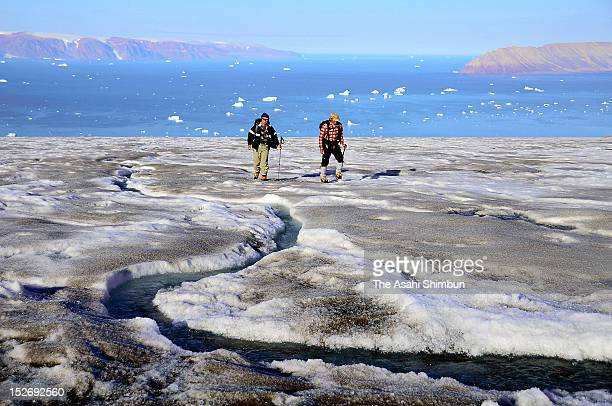 Researchers walk towards a glacier while a stream made by the melting glacier on July 19 2012 near Qaanaaq Greenland In Greenland there is said to be...