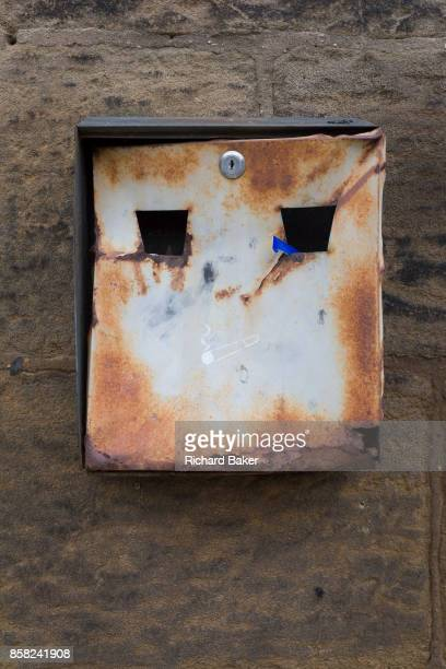 Resembling a punched face is a rusting cigarette receptacle in a Northumbrian town on 26th September 2017 in Alnwick Northumberland England