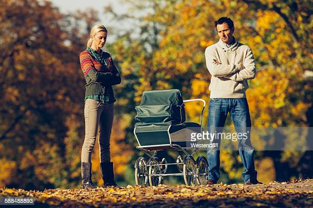 Reserved couple standing with crossed arms looking at baby carriage at autumnal park