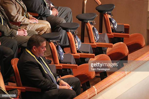 Reserved seats contain American flags and police hats during an interfaith memorial service honoring five slain police officers at the Morton H...